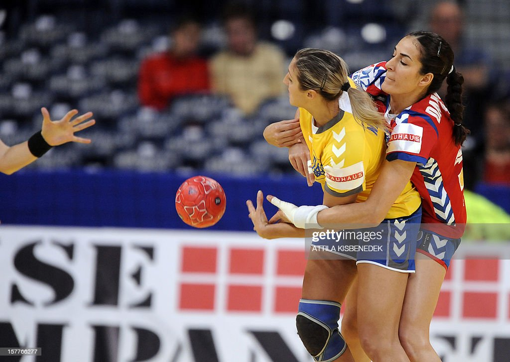Ukraine's Olha Nikolayenko (L) is pushed by Serbia's Sanja Damnjanovic (R) during the 2012 EHF European Women's Handball Championship match on December 6, 2012, at the Kombank Arena of Belgrade. The Serbian capital Belgrade hosts the preliminary round Group A matches including Czech Republic, Norway, Serbia and Ukraine. AFP PHOTO / ATTILA KISBENEDEK