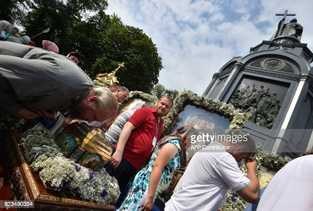 Ukraine's Orthodox Church of Moscow Patriarchy followers kiss icons during a service marking the Day of the Baptism of Kievan Rus in Kiev on July 27...