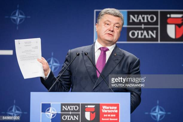 Ukraine's President Petro Poroshenko holds a paper during a joint press conference with the NATO Secretary General after a NATO Summit session on...