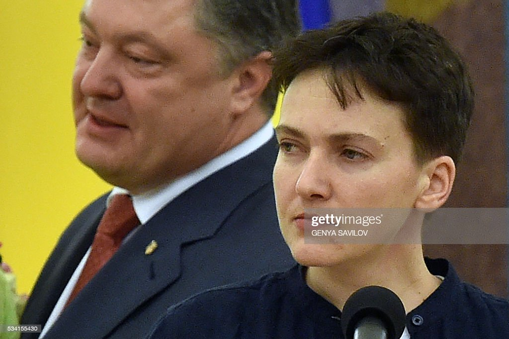 Ukraine's President Petro Poroshenko (L) meets with freed Ukrainian pilot Nadiya Savchenko in Kiev on May 25, 2016. Ukrainian pilot Nadiya Savchenko returned home to a hero's welcome on May 25 after nearly two years in a Russian prison, drawing a line under a damaging diplomatic spat between Moscow and Kiev. The 35-year-old army helicopter pilot flew home as part of an apparent prisoner swap with Moscow, with two alleged Russian soldiers leaving Ukraine earlier in the day. / AFP / GENYA