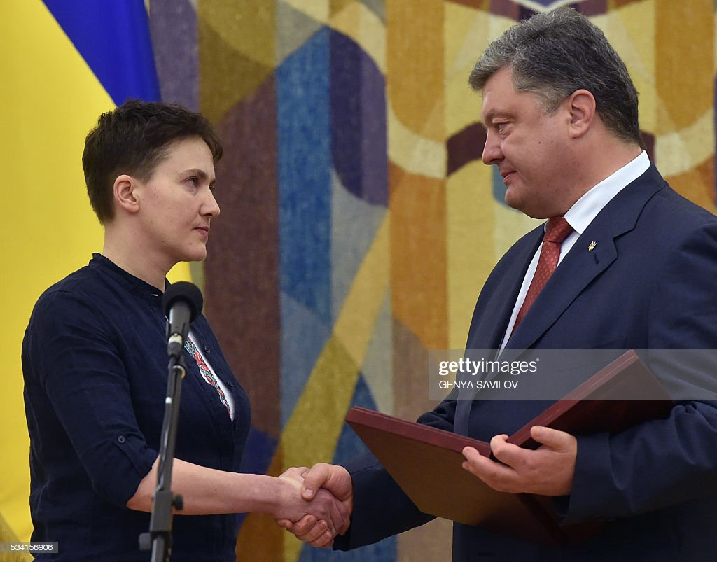 Ukraine's President Petro Poroshenko (R) presents the Hero of Ukraine award to Ukrainian pilot Nadiya Savchenko in Kiev on May 25, 2016. Ukrainian pilot Nadiya Savchenko returned home to a hero's welcome on May 25 after nearly two years in a Russian prison, drawing a line under a damaging diplomatic spat between Moscow and Kiev. The 35-year-old army helicopter pilot flew home as part of an apparent prisoner swap with Moscow, with two alleged Russian soldiers leaving Ukraine earlier in the day. / AFP / GENYA