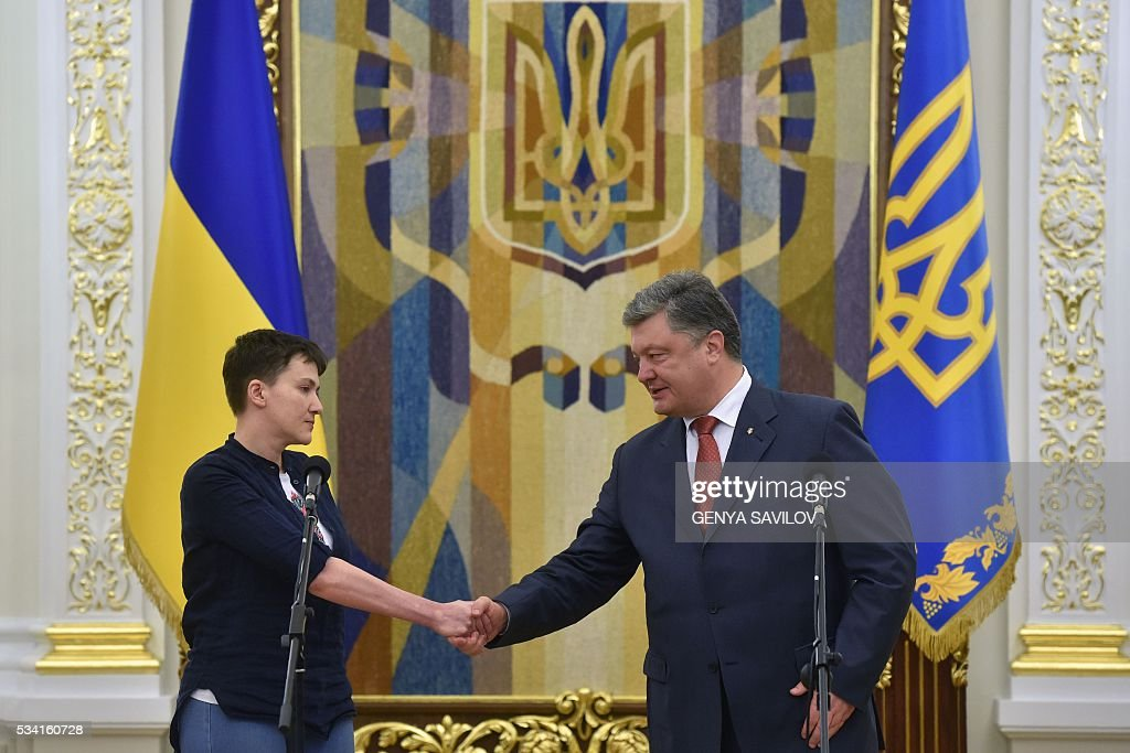 Ukraine's President Petro Poroshenko (R) shakes hands with with freed Ukrainian pilot Nadiya Savchenko during a meeting in Kiev on May 25, 2016. Ukrainian pilot Nadiya Savchenko returned home to a hero's welcome on May 25 after nearly two years in a Russian prison, drawing a line under a damaging diplomatic spat between Moscow and Kiev. The 35-year-old army helicopter pilot flew home as part of an apparent prisoner swap with Moscow, with two alleged Russian soldiers leaving Ukraine earlier in the day. / AFP / GENYA