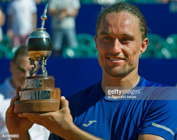 Ukraine's tennis player Alexandr Dolgopolov poses with a trophy as he celebrates winning the Argentina Open after defeating Japan's tennis player Kei...