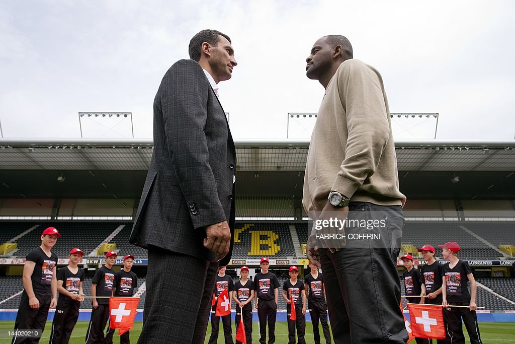 Ukraine's world heavyweight champion Vladimir Klitschko(R) faces his opponent Tony Thompson of the US in front of a Swiss flag during a press conference on May 8, 2012 in Bern ahead of their boxing fight on July at the Stade de Suisse stadium. Klitschko will face Tony 'The Tiger' Thompson in a mandatory defence of his IBF title in Bern.