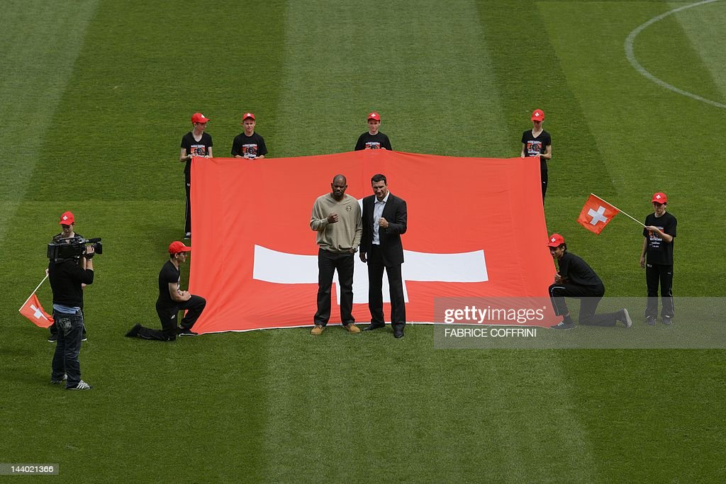 Ukraine's world heavyweight champion Vladimir Klitschko (R) poses with his opponent Tony Thompson of the US in front of a Swiss flag during a press conference on May 8, 2012 in Bern ahead of their boxing fight on July at the Stade de Suisse stadium. Klitschko will face Tony 'The Tiger' Thompson in a mandatory defence of his IBF title in Bern.