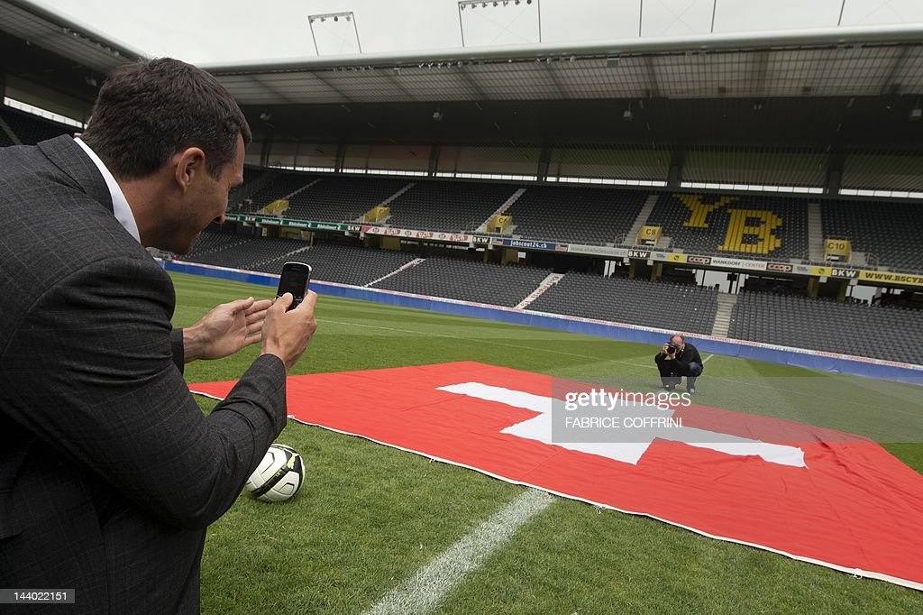Ukraine's world heavyweight champion Vladimir Klitschko snaps with his mobile phone a picture of a Swiss flag in the center of the Stade de Suisse stadium during a press conference on July 8, 2012 ahead of his boxing fight at the Stade de Suisse stadium. Klitschko will face Tony 'The Tiger' Thompson in a mandatory defence of his IBF title in Bern. AFP PHOTO / FABRICE COFFRINI