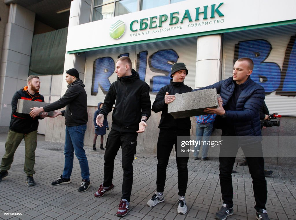 Ukrainian activists from National corps build a wall of cinder blocks at the entrance a branch of Sberbank of Russia,during their protest in Kiev, Ukraine, 13 March 2017. Activists and supporters of Ukrainian nationalist groups demanded that the National Bank of Ukraine to close all banks associated with Russia in Ukraine.
