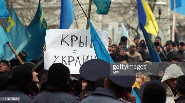 Ukrainian activists hold a placard reading 'Crimea = Ukraine' during a rally in front of Crimean parliament in Simferopol on February 26 2014 A man...