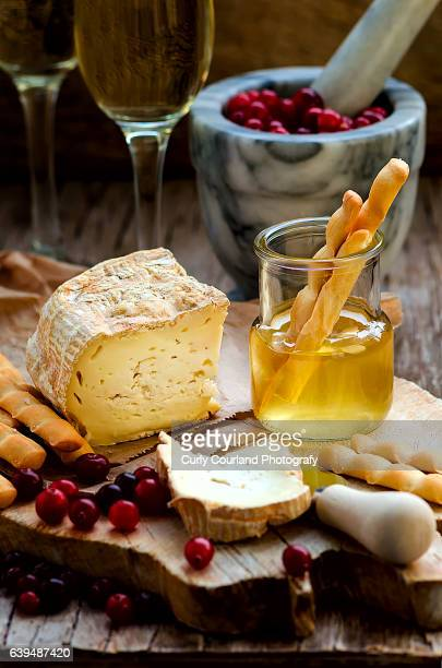 Ukrainian artisanal soft cheese Premiera with cranberries, honey and grissini breadsticks served on the vintage wooden cutting board on the rustic wooden background with cheese knife, marble mortar and glass of white wine are on the background