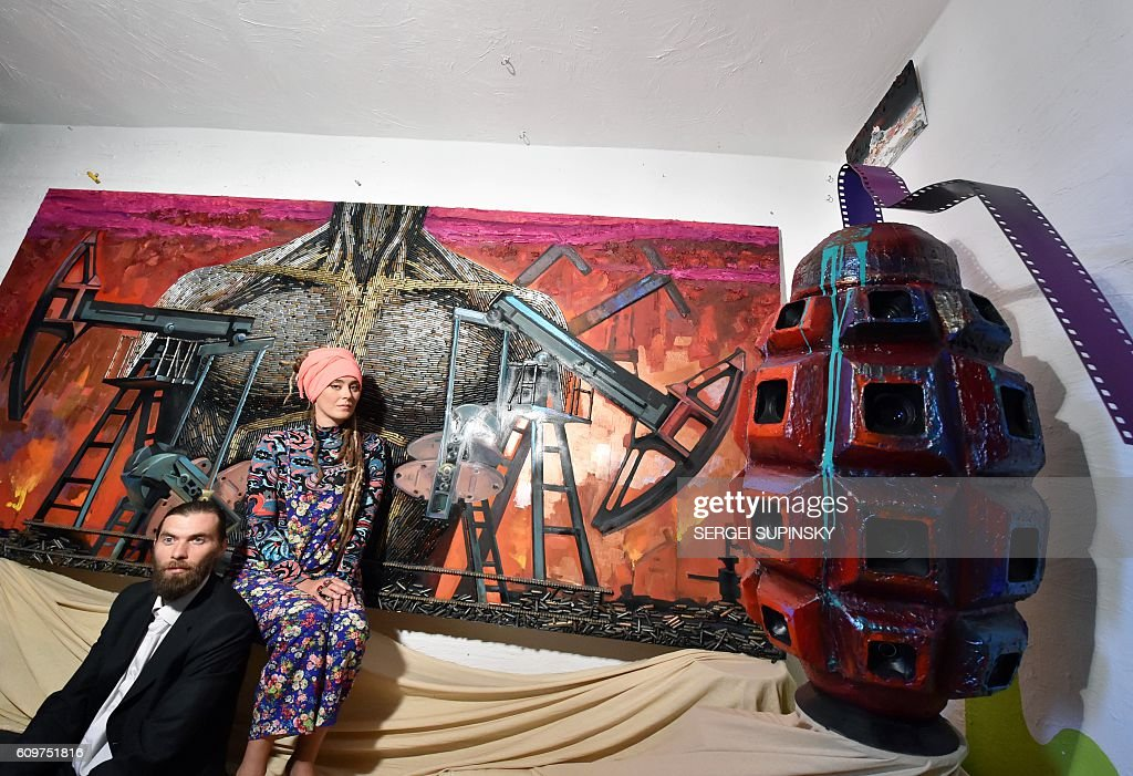 Ukrainian artists Daria Marchenko and Daniel Green well known for their portrait of Russian President Vladimir Putin made from bullet shells, speak as they sit in front of their artwork called 'The Brain of War' (R) and 'The heart of the war' (back) during the presentation of five new creations under the title 'The evolution of dictate' in their small apartment-studio in Kiev on September 22, 2016. The artists used cartridge cases -guns, sniper rifles, fragments of missiles 'Grad', mortar shells- and shoulder straps of countries who guaranteed Ukrainian security under the Budapest Memorandum - Ukraine, Russia, the United States, Britain, China, France. CAPTION