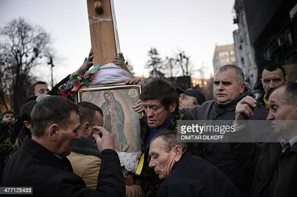Ukrainian Catholics carry a huge wooden cross during a religious procession near the Dinamo stadium close to Independence square in central Kiev on...
