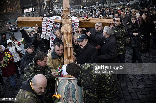 Ukrainian Catholics set up a huge wooden cross during a religious procession near the Dinamo stadium close to Independence square in central Kiev on...