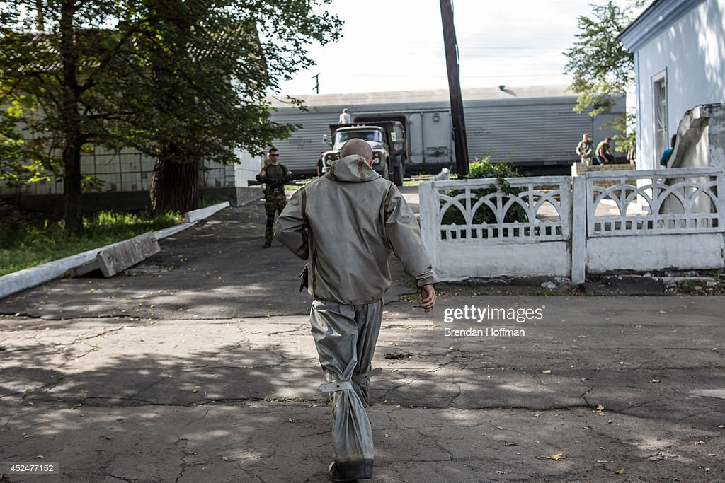 A Ukrainian Emergencies Ministry worker wears a rubber suit before transfering the bodies of victims of the crash of Malaysia Airlines flight MH17 from a truck into a refrigerated train car on July 21, 2014 in Torez, Ukraine. Malaysia Airlines flight MH17 was travelling from Amsterdam to Kuala Lumpur when it crashed killing all 298 on board including 80 children. The aircraft was allegedly shot down by a missile and investigations continue over the perpetrators of the attack.
