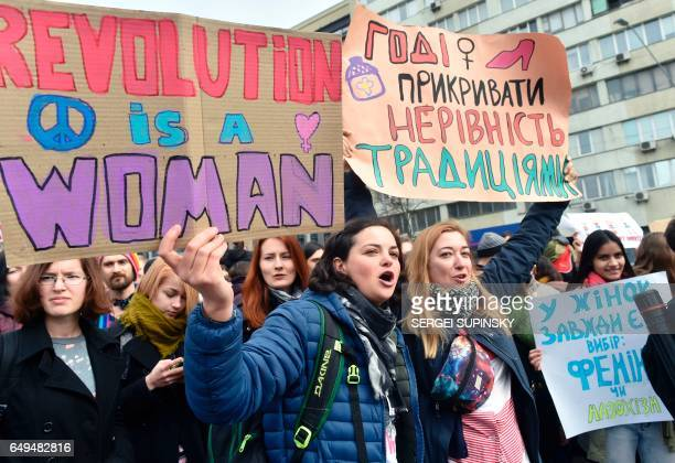 Ukrainian feminists hold placards reading 'Revolution is a woman' and 'Enough to cover inequality with traditions' during a march on March 8 2017 in...