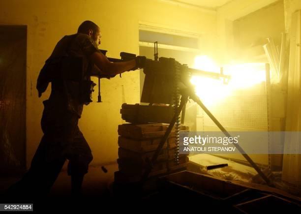 Ukrainian Forces soldier fires a heavy machine gun during a battle with proRussian separatists at Avdeyevka in Ukraine's Donetsk region on June 25...