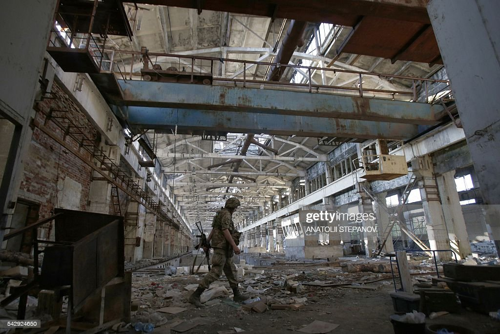 A Ukrainian Forces soldier walks through a shell-damaged factory during a battle with pro-Russian separatists at Avdeyevka, in Ukraine's Donetsk region on June 25, 2016. / AFP / ANATOLII