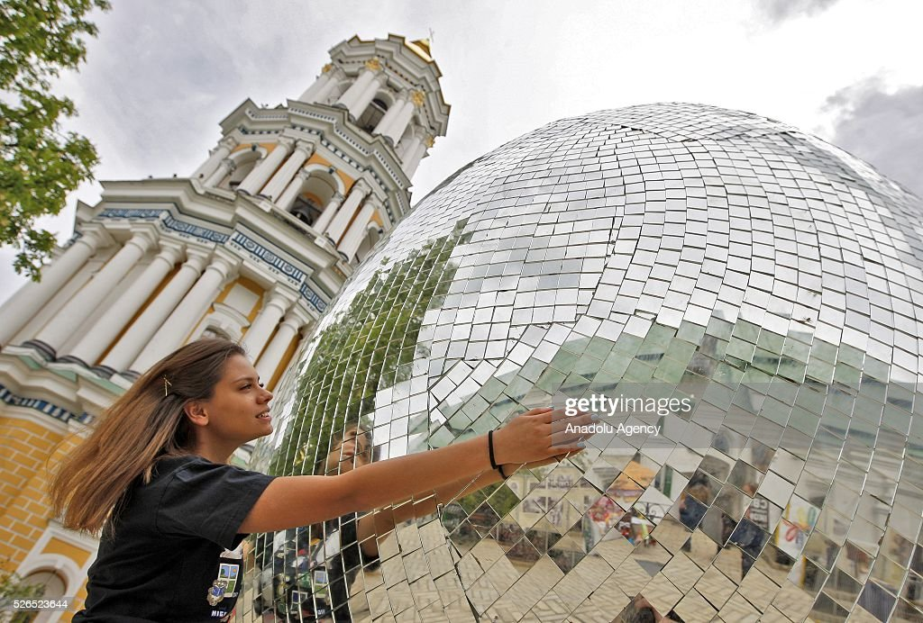 Ukrainian girl hugging a giant egg, named 'Diamond Easter Egg',3.5 m high, which is decorated with more than 15,000 mirror particles during the Ukrainian Easter hand made fair 'Easter country' at the Kiev-Pechersk Lavra in Kiev, Ukraine on April 30, 2016.