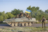 Ukrainian government soldiers sit on top of an armoured vehicle as they take up a position almost 20Km south of Donetsk on on July 9 2014 in Donetsk...