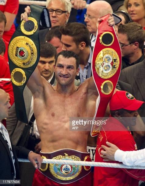 Ukrainian IBF and WBO world champion Wladimir Klitschko holds up the belts after the fight against British WBA champion David Haye in the northern...