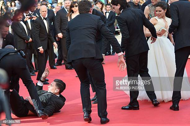 Ukrainian journalist Vitalii Sediuk is dragged away by minders after he tried to slip under US actress America Ferrera's dress as she arrives for the...