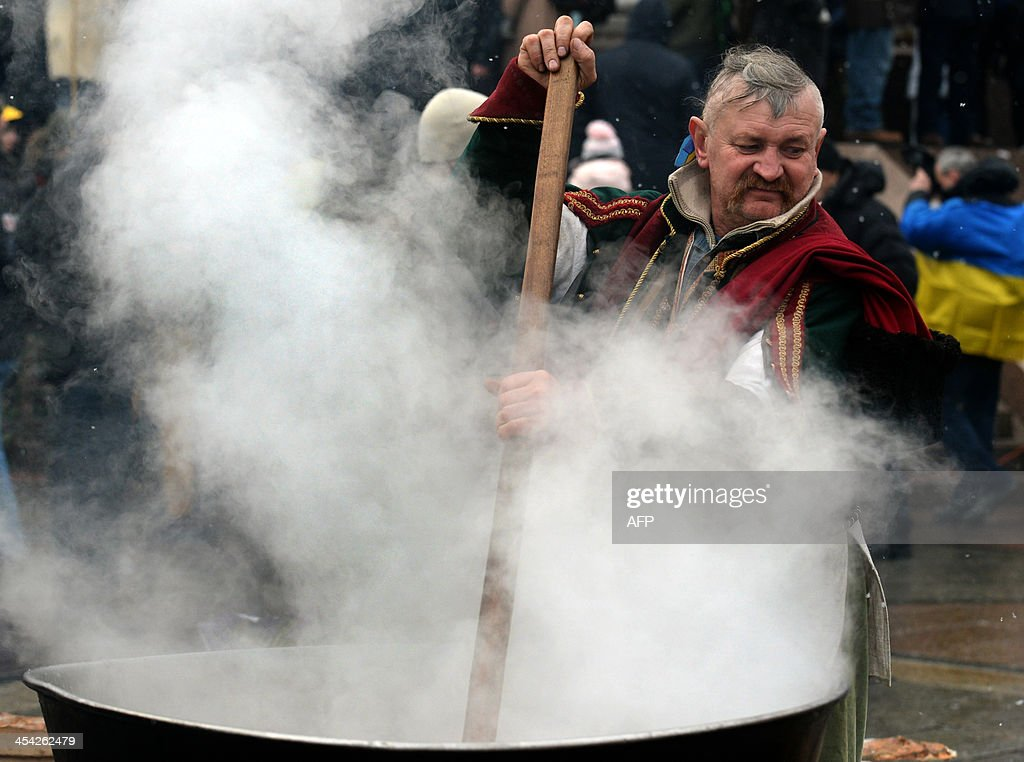 A Ukrainian man serves soup at a camp set up by opposition demonstrators on Kiev's Independence Square on December 8, 2013. Hundreds of thousands of pro-EU Ukrainians rallied in Kiev on December 8 for a new protest aimed at forcing President Viktor Yanukovych to resign after he sparked fury by rejecting an EU pact under Kremlin pressure.