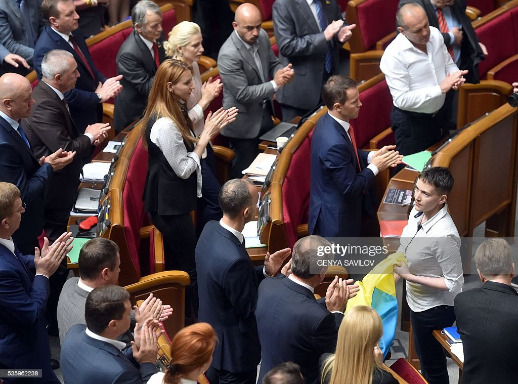 Ukrainian MPs applaud Nadiya Savchenko (R) at the Ukrainian Parliament in Kiev on May 31, 2016. Savchenko takes part today in a Parliament session as Ukrainian MP. The 35-year-old army helicopter pilot, elected as an MP in absentia during almost two years in a Russian jail, also raised the possibility she could run for president. / AFP / GENYA