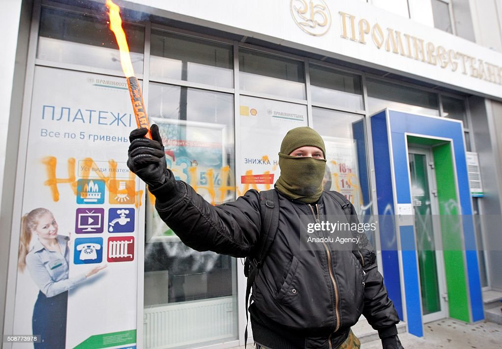 Ukrainian Nationalist organization Right sector member lights torch in front of Prominvestbank during a protest against 'Russian business in Ukraine' in Kiev, Ukraine on February 06, 2016.