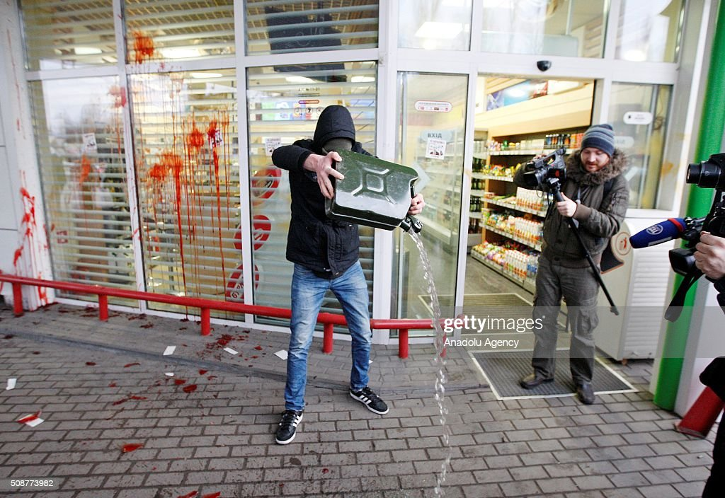 Ukrainian Nationalist organization Right sector member pours gass at gass station during a protest against 'Russian business in Ukraine' in Kiev, Ukraine on February 06, 2016.