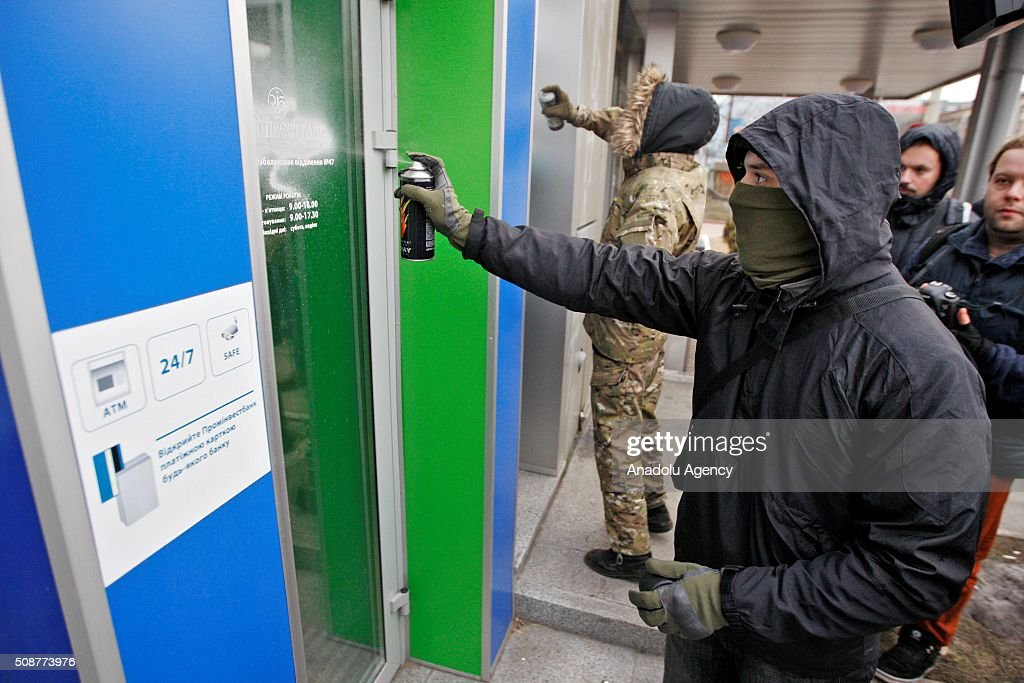 Ukrainian Nationalist organization Right sector members paint the windows of Prominvestbank during a protest against 'Russian business in Ukraine' in Kiev, Ukraine on February 06, 2016.