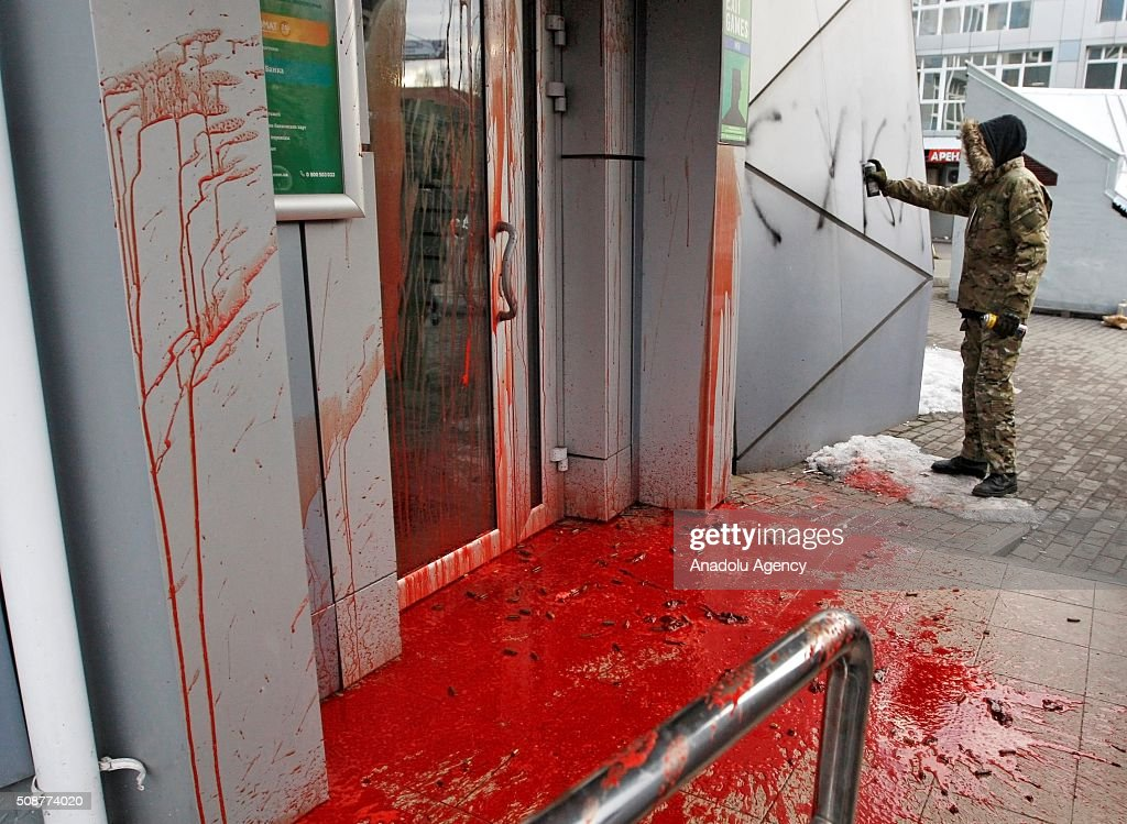 Ukrainian Nationalist organization Right sector members paint the main entrance of Russia's Sberbank during a protest against 'Russian business in Ukraine' in Kiev, Ukraine on February 06, 2016.