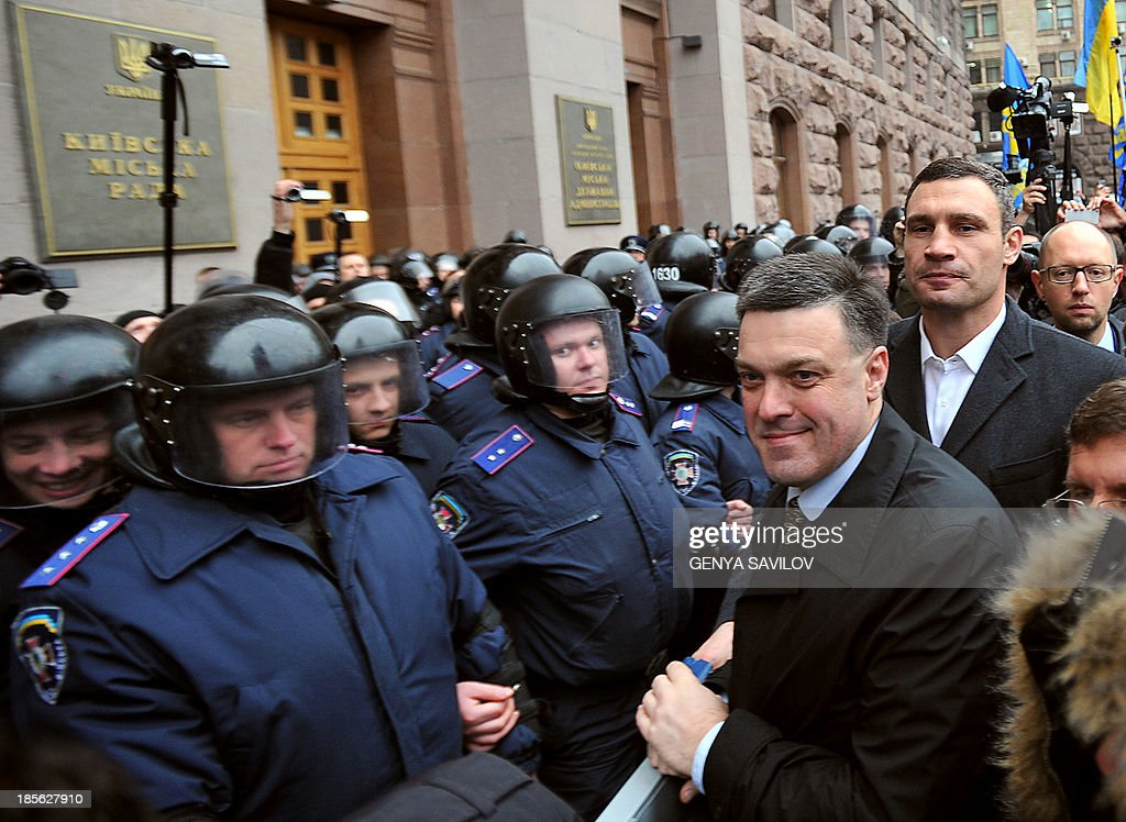 Ukrainian opposition leaders Oleh Tyahnybok (3rd R), Vitaliy Klitschko (2nd R) and Arseniy Yatsenyuk (R) walk in front riot police as they try to enter of Kiev's city council building and block a session on October 23, 2013 in Kiev. Several hundred of people rallied at the Kiev city administration trying to break the city council session and demand to hold council elections. The credentials of the city's deputies ended on July 2, 2013, and the opposition insists that their session is illegal.