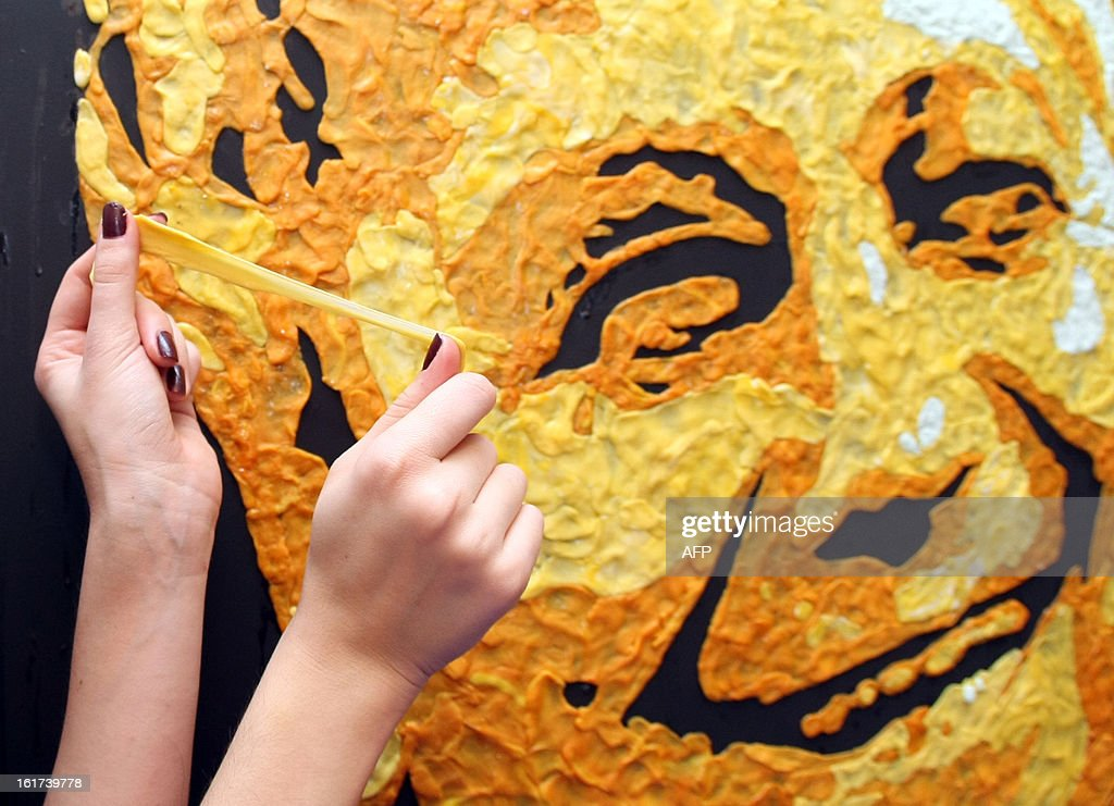 Ukrainian painter Anna-Sofiya Matveeva, 22, uses chewed chewing gum during her work to create a portrait of the football club Shakhtar coach Mircea Lucescu in her studio in small Ukrainian city of Makiyivka on February 15, 2013. Some 800 chewed chewing gums were used for the the creation, some 1000 chewing gums - for the portrait of Steve Jobs made one month before and the 500 gums for the portrait of British rock-star Elton John, still a work in progress. AFP PHOTO/ALEXANDER KHUDOTEPLY