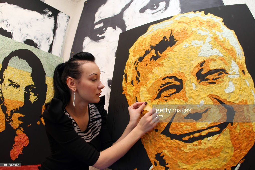 Ukrainian painter Anna-Sofiya Matveeva, 22, uses chewed chewing gum during her work to create a portrait of the football club Shakhtar coach Mircea Lucescu in her studio in small Ukrainian city of Makiyivka on February 15, 2013. Some 800 chewed chewing gums were used for the the creation, some 1000 chewing gums - for the portrait of Steve Jobs made one month before and the 500 gums for the portrait of British rock-star Elton John, still a work in progress.