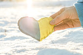 Woman holding ukrainian flag in a form of a heart over sunshine in winter scenery