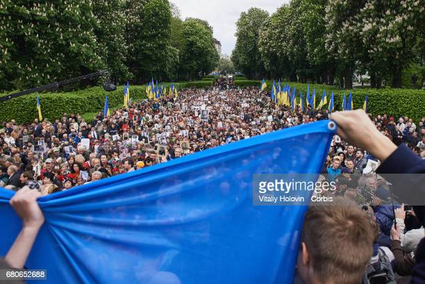 Ukrainian patriots hold the flag of Ukraine during Victory Day celebrations in front of the Tomb of the Unknown Soldier on May 9 2017 in Kiev Ukraine...