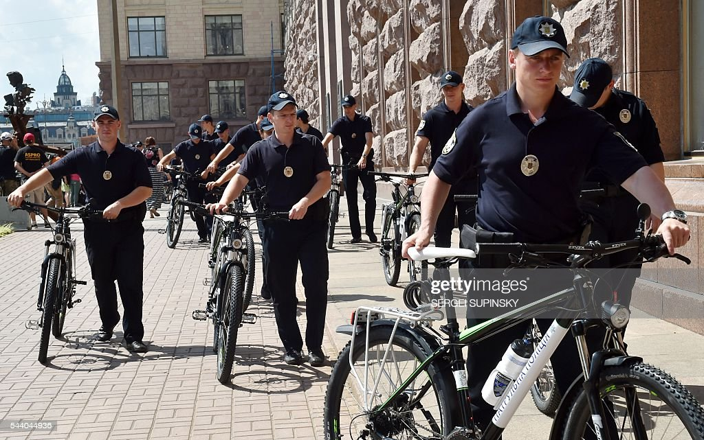 Ukrainian patrol policemen carry bicycles handed to them by former World Boxing Champion, Kiev Mayor Vitali Klitschko during a ceremony to present bicycles to the Kiev police, in front of city hall of Kiev on July 1, 2016. Klitschko handed over 100 bicycles to the Kiev police for patrolling the Ukrainian capital. / AFP / SERGEI
