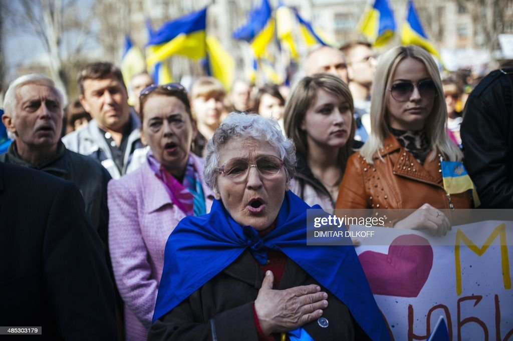 Ukrainian people sing their national anthem during a nationalist and pro-unity rally in the eastern city of Lugansk on April 17, 2014. Russia's Foreign Minister Sergei Lavrov today announced a deal had been reached with Ukraine, the United States and the European Union to 'de-escalate' dangerously high tensions in the former Soviet republic.