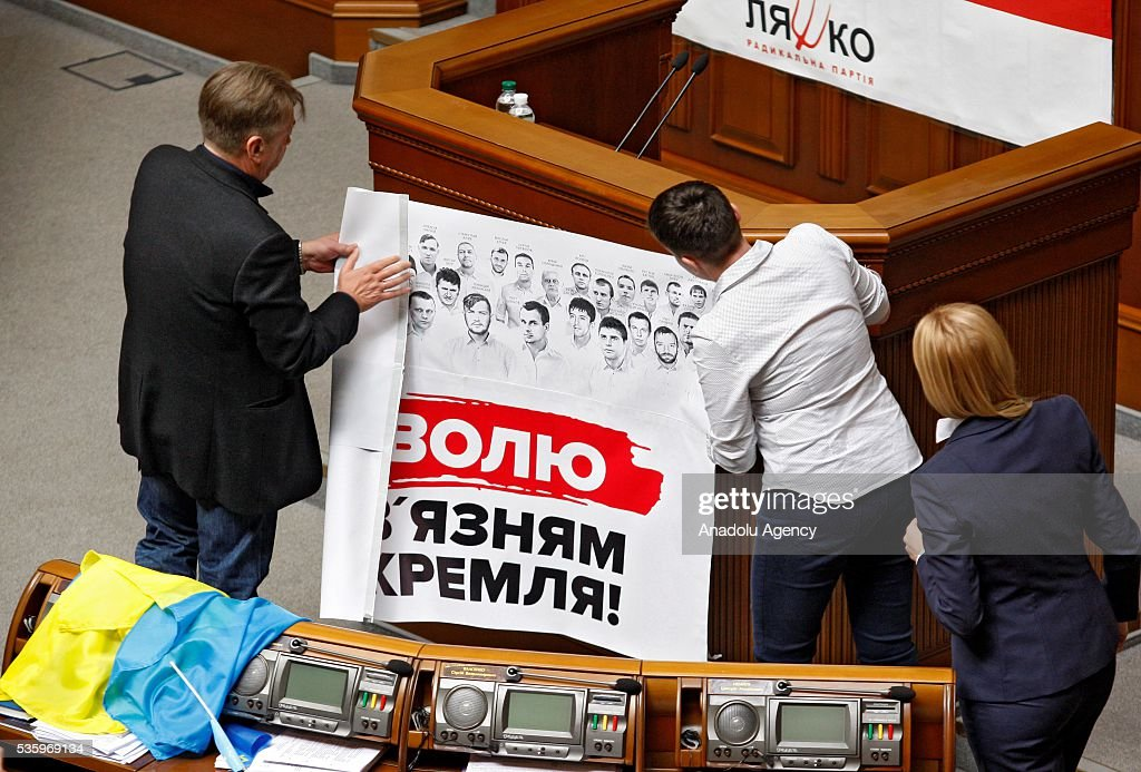 Ukrainian pilot and Ukrainian parliament member Nadiya Savchenko (C) and lawmakers set up a poster saying 'Freedom to the captives of Kremlin' on the rostrum during a session of Parliament in Kiev, Ukraine on May 31, 2016.