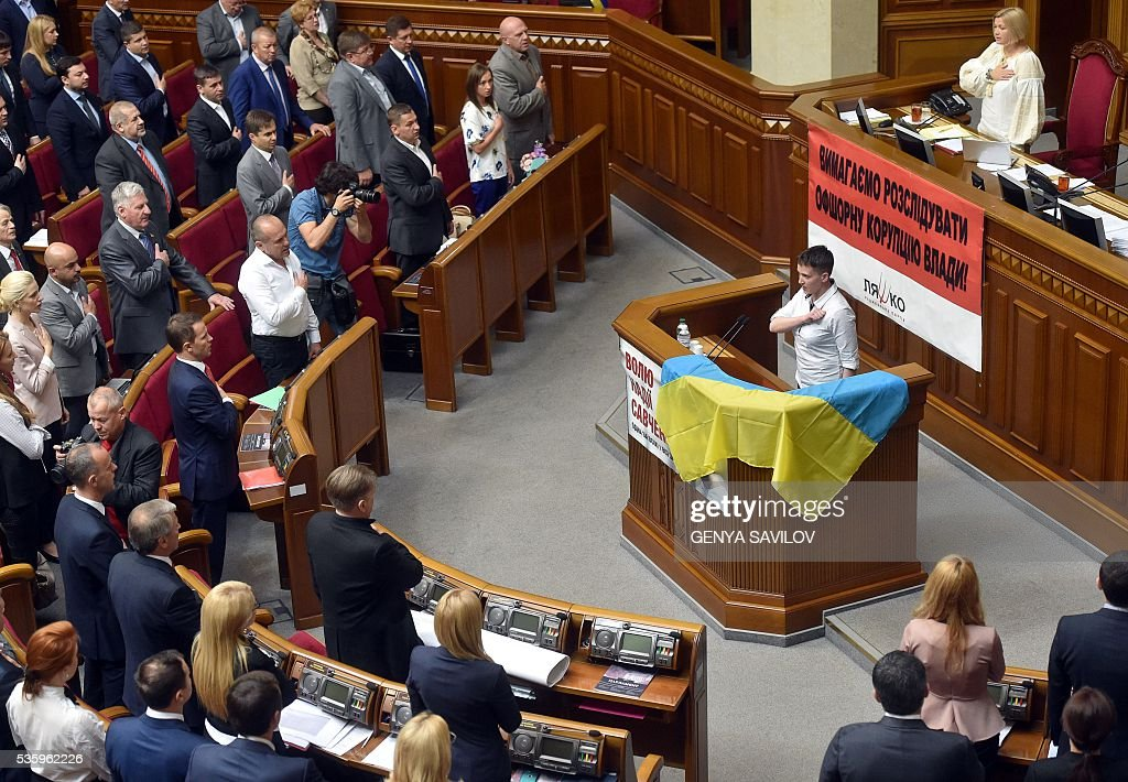 Ukrainian pilot Nadiya Savchenko (C) and Ukrainian MPs sing the national anthem at the Ukrainian Parliament in Kiev on May 31, 2016. Savchenko takes part today in a Parliament session as Ukrainian MP. The 35-year-old army helicopter pilot, elected as an MP in absentia during almost two years in a Russian jail, also raised the possibility she could run for president. / AFP / GENYA