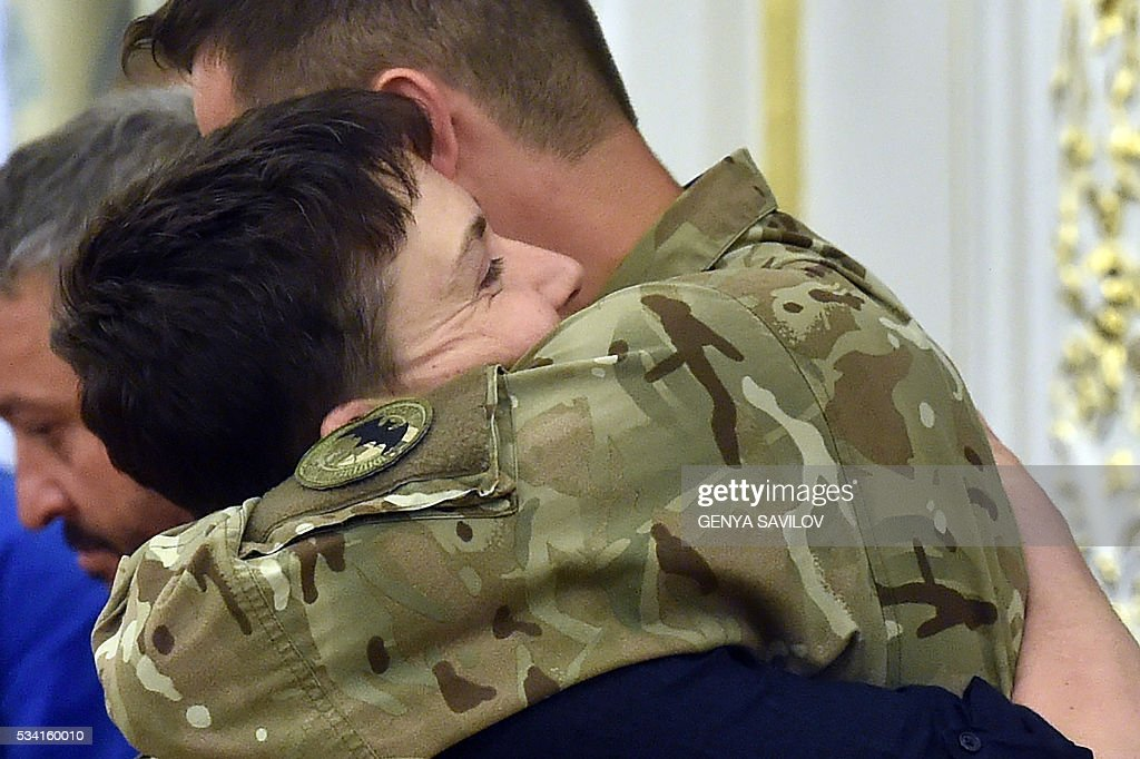 Ukrainian pilot Nadiya Savchenko embraces a serviceman from the Aydar battalion during a meeting with Ukraine's President in Kiev on May 25, 2016. Ukrainian pilot Nadiya Savchenko returned home to a hero's welcome on May 25 after nearly two years in a Russian prison, drawing a line under a damaging diplomatic spat between Moscow and Kiev. The 35-year-old army helicopter pilot flew home as part of an apparent prisoner swap with Moscow, with two alleged Russian soldiers leaving Ukraine earlier in the day. / AFP / GENYA