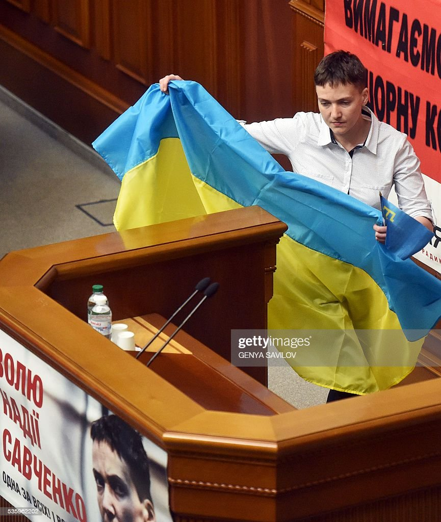Ukrainian pilot Nadiya Savchenko holds Ukrainian and Crimean Tatars flags as she walks to a rostrum at the Ukrainian Parliament in Kiev on May 31, 2016. Savchenko takes part today in a Parliament session as Ukrainian MP. The 35-year-old army helicopter pilot, elected as an MP in absentia during almost two years in a Russian jail, also raised the possibility she could run for president. / AFP / GENYA