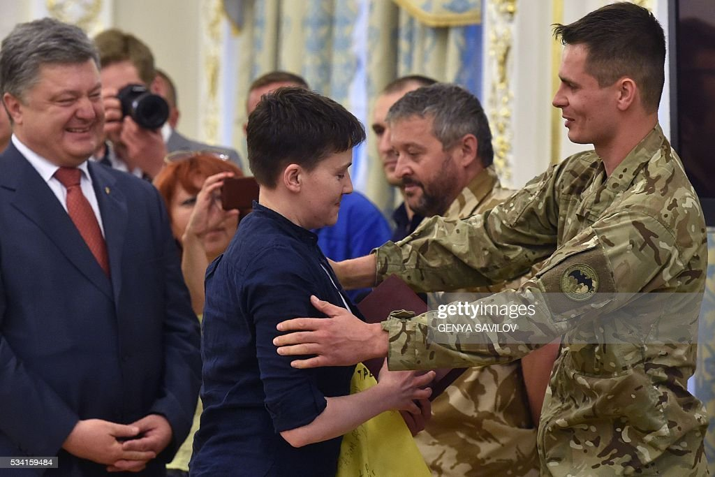 Ukrainian pilot Nadiya Savchenko (C) is greeted by servicemen from the Aydar battalion as Ukraine's President Petro Poroshenko stands beside during a ceremony in Kiev on May 25, 2016. Ukrainian pilot Nadiya Savchenko returned home to a hero's welcome on May 25 after nearly two years in a Russian prison, drawing a line under a damaging diplomatic spat between Moscow and Kiev. The 35-year-old army helicopter pilot flew home as part of an apparent prisoner swap with Moscow, with two alleged Russian soldiers leaving Ukraine earlier in the day. / AFP / GENYA