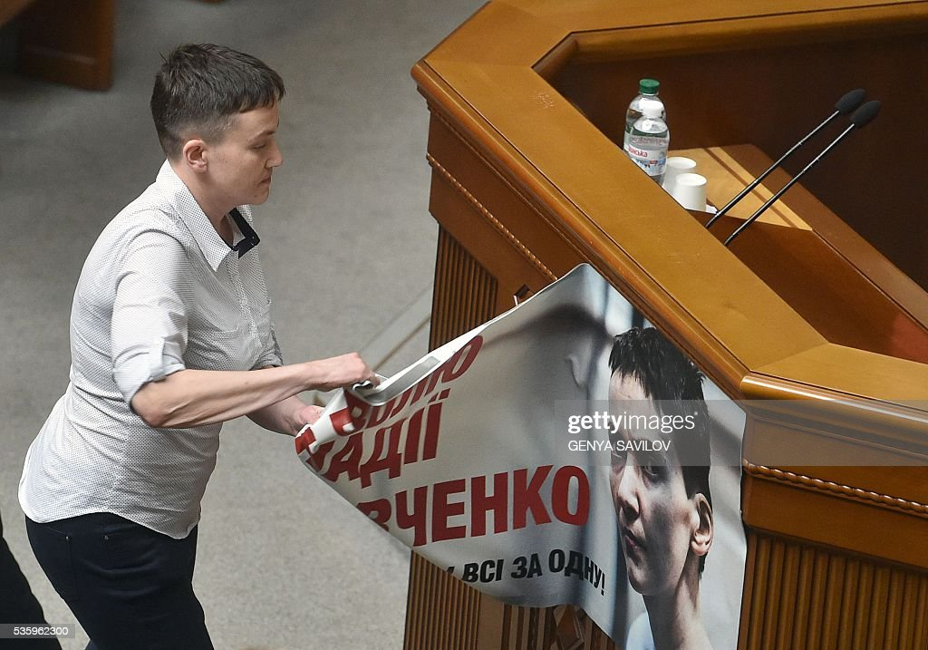 Ukrainian pilot Nadiya Savchenko removes a placard depicting her in a jail, from a rostrum at the Ukrainian Parliament in Kiev on May 31, 2016. Savchenko takes part today in a Parliament session as Ukrainian MP. The 35-year-old army helicopter pilot, elected as an MP in absentia during almost two years in a Russian jail, also raised the possibility she could run for president. / AFP / GENYA
