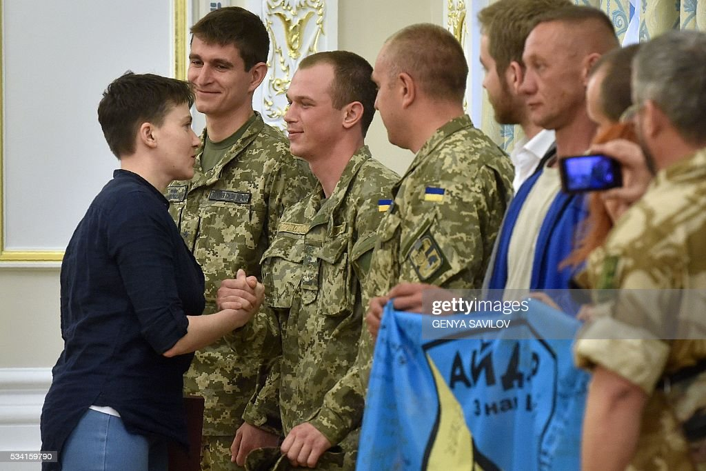 Ukrainian pilot Nadiya Savchenko (L) shakes hands with servicemen from the Aydar battalion during a meeting with Ukraine's President in Kiev on May 25, 2016. Ukrainian pilot Nadiya Savchenko returned home to a hero's welcome on May 25 after nearly two years in a Russian prison, drawing a line under a damaging diplomatic spat between Moscow and Kiev. The 35-year-old army helicopter pilot flew home as part of an apparent prisoner swap with Moscow, with two alleged Russian soldiers leaving Ukraine earlier in the day. / AFP / GENYA