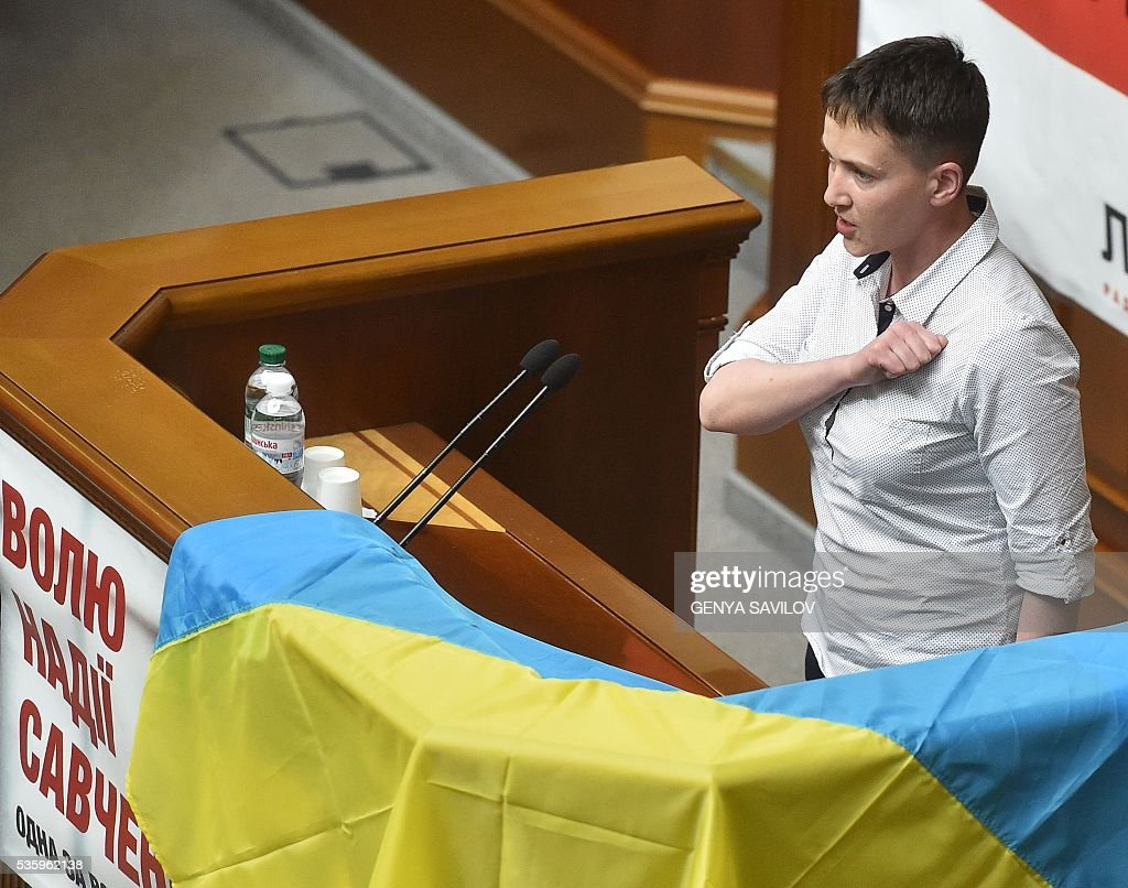 Ukrainian pilot Nadiya Savchenko sings the Ukranian national anthem as she stands on a rostrum at the Ukrainian Parliament in Kiev on May 31, 2016 Savchenko takes part today in a Parliament session as Ukrainian MP. The 35-year-old army helicopter pilot, elected as an MP in absentia during almost two years in a Russian jail, also raised the possibility she could run for president. / AFP / GENYA
