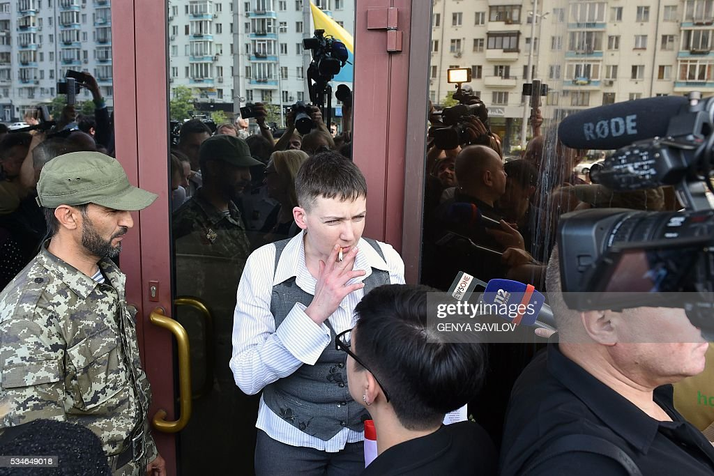 Ukrainian pilot Nadiya Savchenko (C) smokes a cigarette while speaking to media after a press conference in Kiev on May 27, 2016. Savchenko returned home to a hero's welcome on May 25 after nearly two years in a Russian jail following a prisoner swap with Moscow that drew a line under a major diplomatic spat. The 35-year-old army helicopter pilot flew home as part of a carefully choreographed exchange with Moscow, with two alleged Russian soldiers leaving Ukraine earlier in the day SAVILOV