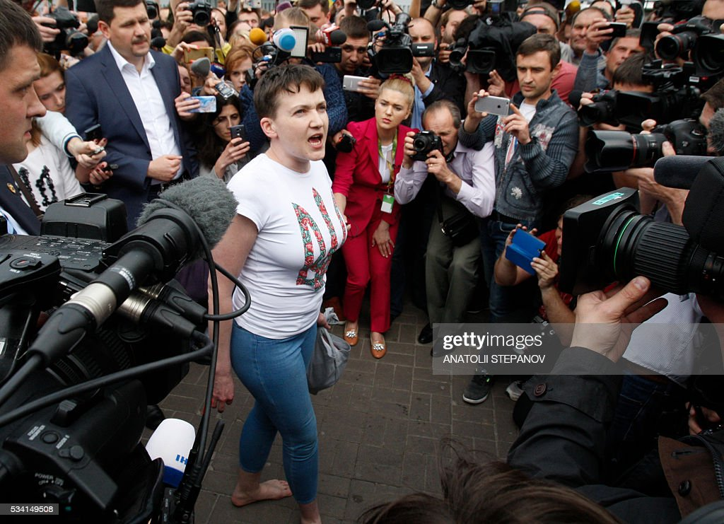 Ukrainian pilot Nadiya Savchenko (C), who was freed from jail in Russia as part of a prisoner exchange, talks to the media upon arrival at Kiev's Boryspil airport on May 25, 2016. Ukrainian pilot Nadiya Savchenko, who had spent nearly two years in a Russian prison, returned home to a hero's welcome on May 25, drawing the curtain on one of the most serious diplomatic problems between Moscow and Kiev. The 35-year-old army helicopter pilot returned home as part of an apparent swap with Moscow, after two alleged Russian soldiers, Aleksandr Aleksandrov and Yevgeny Yerofeyev, left Ukraine earlier in the day. / AFP / ANATOLII