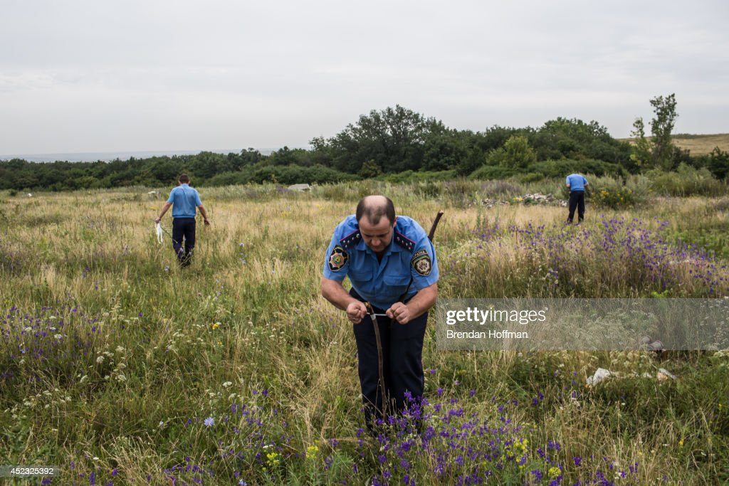 Ukrainian police officer ties a white ribbon to a stake to mark human remains found in a field on July 18 2014 in Grabovka Ukraine Malaysia Airlines...
