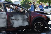 Ukrainian police officers and security services experts examine the charred car of journalist Pavel Sheremet after he was killed in a car bomb in...
