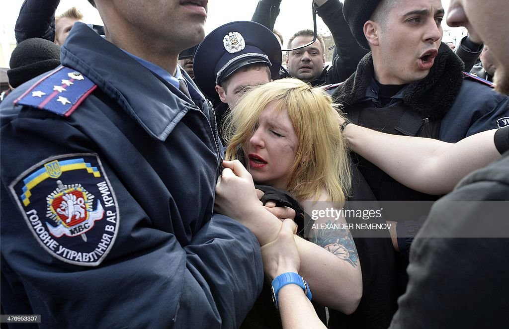 Ukrainian police officers detain a topless activist of the Ukrainian women movement Femen, protesting against the war in front of Cremea's parliament during a pro-Russian rally in Simferopol on March 6, 2014 .